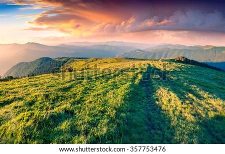 Colorful summer sunrise in the Carpathian mountains. First sunlight glowing mountainsides on Svidovets ridge, Ukraine, Europe. - stock photo