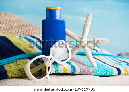 Colorful summer towel,  sunglasses, lotion and starfish on sand beach.  - stock photo
