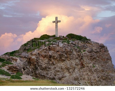 colorful sundown scenery on a caribbean island named Guadeloupe including a summit cross on mountain top - stock photo