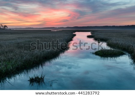 Colorful Sunrise Over Inlet with Water Reflections - stock photo