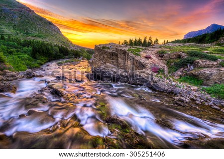 Colorful sunrise over the rapids of Swiftcurrent Creek in Glacier National Park, Montana - stock photo