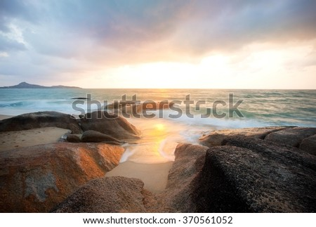 Colorful sunrise over the sea and rocks - long exposure.