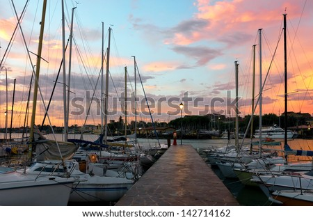 Colorful sunrise over the yacht marina in Desenzano del Garda in Italy, tranquil scene with sail boats, quay and lamp post. - stock photo
