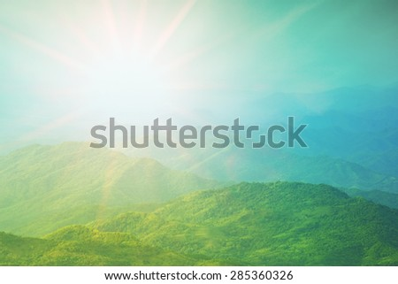 Colorful sunrise over valley in the morning with misty sky - stock photo