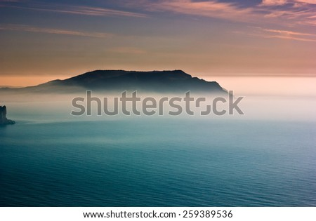 colorful sunrise with haze above cape in Black Sea with blue water and red sky - stock photo