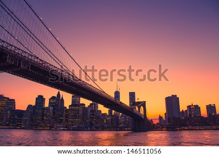 Colorful sunset over New York City skyline and Brooklyn Bridge - stock photo