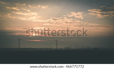 Colorful sunset over the fields in countryside with dramatic clouds - vintage film effect