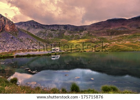 Colorful sunset over the Lake Essaupres located at 2306 m altitude near one of the highest asphalted road in Europe which lead to Col de la Bonette (2715 m) in Alpes-de-Haute-Provence, south of France - stock photo
