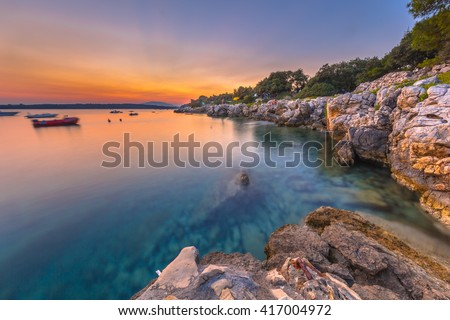 Colorful sunset over the rocky coast of Croatia. Long exposure image of sunset, rocks, boats and turqoise water on the Island of Cres.