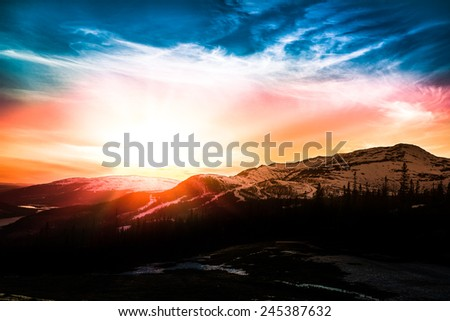 colorful sunset over the ski resort in the mountains with forest in the foreground - stock photo