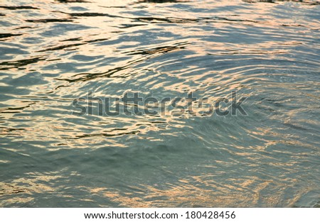 Colorful Sunset reflections on water surface - stock photo