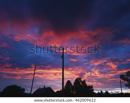 Colorful sunset with purple and yellow, red, orange, blue colors of sky. Russian village landscape. Countryside mobile photo.