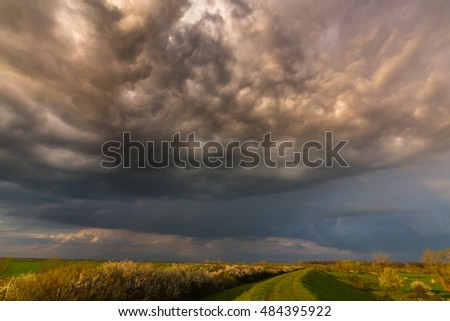 Colorful sunset with storm clouds and rainbow