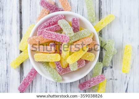 Colorful sweet and sour Gummi Candy (close-up shot) on bright wooden background (selective focus) - stock photo