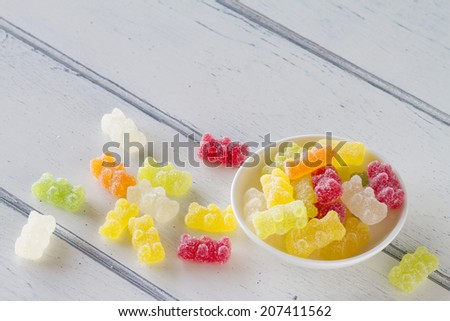 Colorful sweet gummy bears with sugar on a white wooden table. Vintage style.. - stock photo