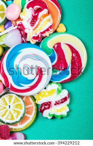 Colorful sweets and candies on a green background