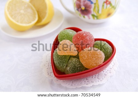 Colorful sweets in a heart-shape vase in a tea table, close up - stock photo