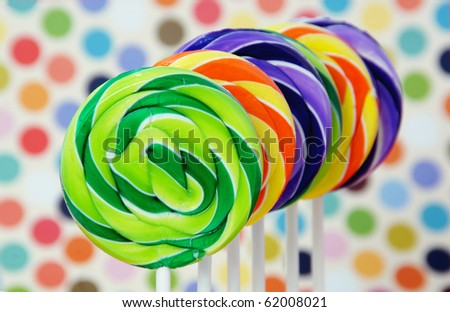Colorful swirled lollipops on a party background - stock photo