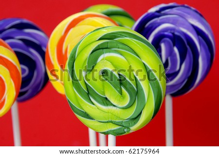 Colorful swirled lollipops on a red background - stock photo