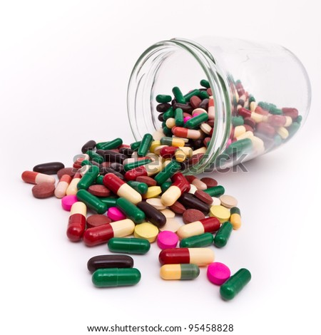 colorful tablets and capsules in glass container