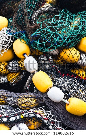 Colorful tangled fishing net with floats - stock photo
