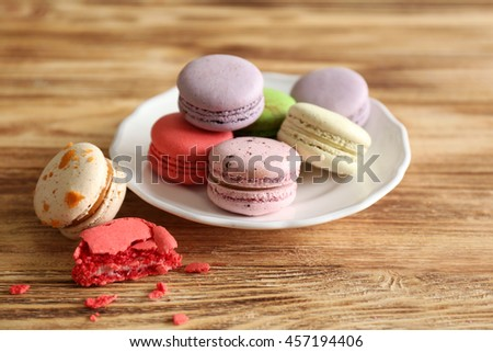 Colorful tasty macaroons in plate on wooden background - stock photo