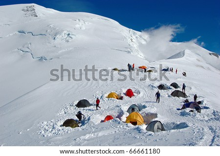 Colorful tents in high snowy mountains, (Refuge du Goater) halfway up Mont Blanc in France - stock photo