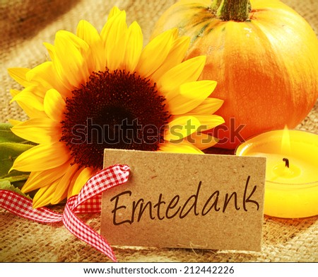Colorful Thanksgiving background with a gift tag with the German word - Erntedank - with a vibrant yellow sunflower orange pumpkin and burning candle grouped on rustic hessian - stock photo