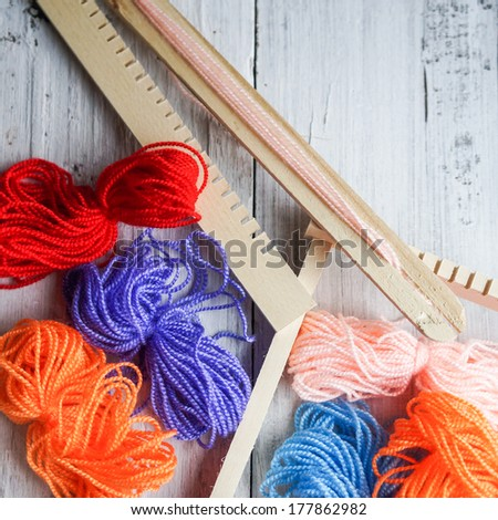 Colorful threads and loom. Hobby for a kid - stock photo