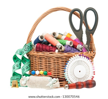 Colorful threads in a wicker basket with sewing accessories on white background - stock photo