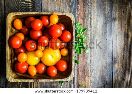 Colorful tomatoes on rustic background - stock photo