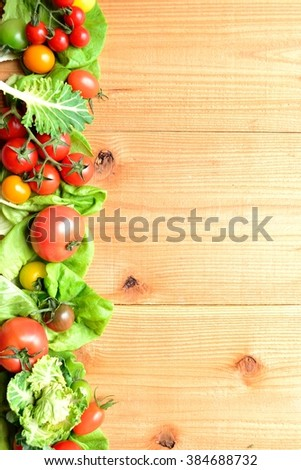 Colorful tomatoes with green leaves on the wooden background.frame