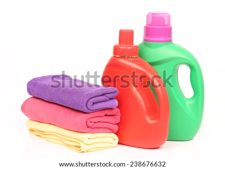 Colorful towels and liquid laundry detergent over white background - stock photo