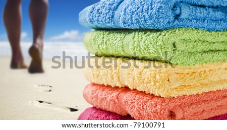 Colorful towels and someone walking on the beach - stock photo