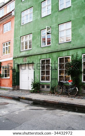 Colorful town houses in street in Copenhagen. pavement with bike and apartments or flats - stock photo