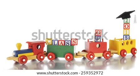 """Colorful toy train hauling alphabet block saying, """"Class of 2015"""" which is topped with a graduation cap and tassel.  On a white background. - stock photo"""