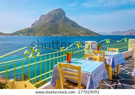 Colorful traditional Greek restaurant with view on sea and remote Island, Greece - stock photo