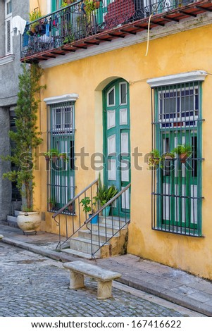 Colorful traditional house in Old Havana with flower pots and plants on its windows - stock photo