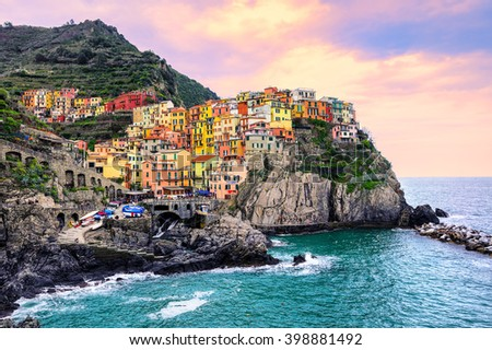 Colorful traditional houses on a rock over Mediterranean sea on dramatic sunset, Manarola, Cinque Terre, Italy