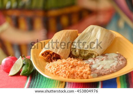 Colorful Traditional Mexican food dishes tamales, rice and beans - stock photo