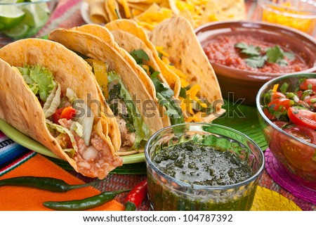 Colorful Traditional Mexican food dishes: various fajitas, nachos, tomato salsa, salsa cruda served on a beautifully decorated table - stock photo
