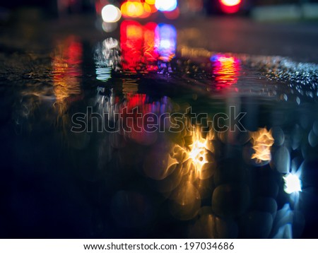 Colorful traffic lights bokeh circles reflecting in water on night city street. Abstract background. - stock photo