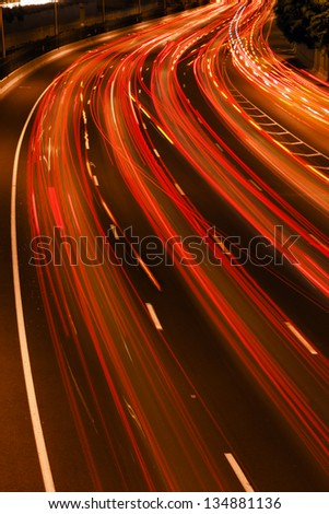 Colorful trails of light is all that remains from the swift highway traffic. - stock photo