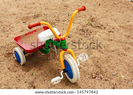 Colorful tricycles for kid on sand floor - stock photo