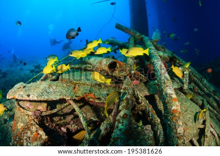 Colorful tropical fish and SCUBA divers swim around the manmade debris of an abandoned oil rig - stock photo