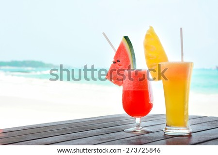 Colorful tropical fruit smoothies on the table at the beach - soft focus - stock photo