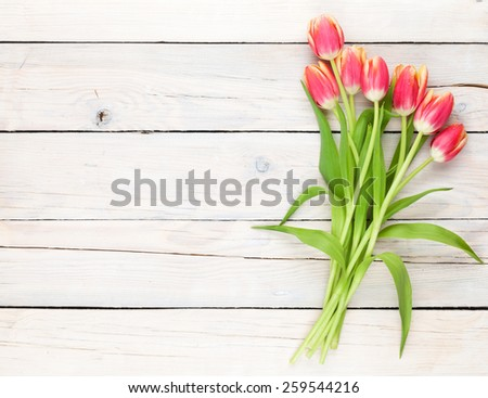 Colorful tulips on wooden table. Top view with copy space - stock photo