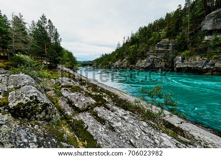 Colorful turquoise river and shore with rocks and trees in Norway