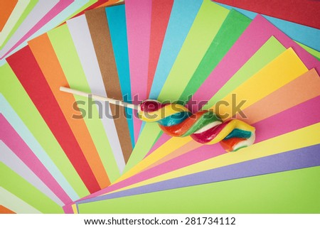Colorful twisted sweet lollipop and brightly colored papers background. Rainbow theme. - stock photo