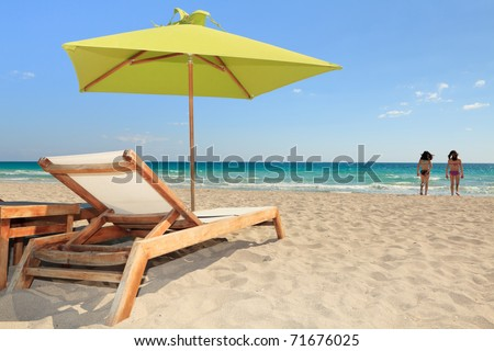 Colorful umbrella and lounge chair in the trendy and popular South Beach in Miami with young bathers in the background.